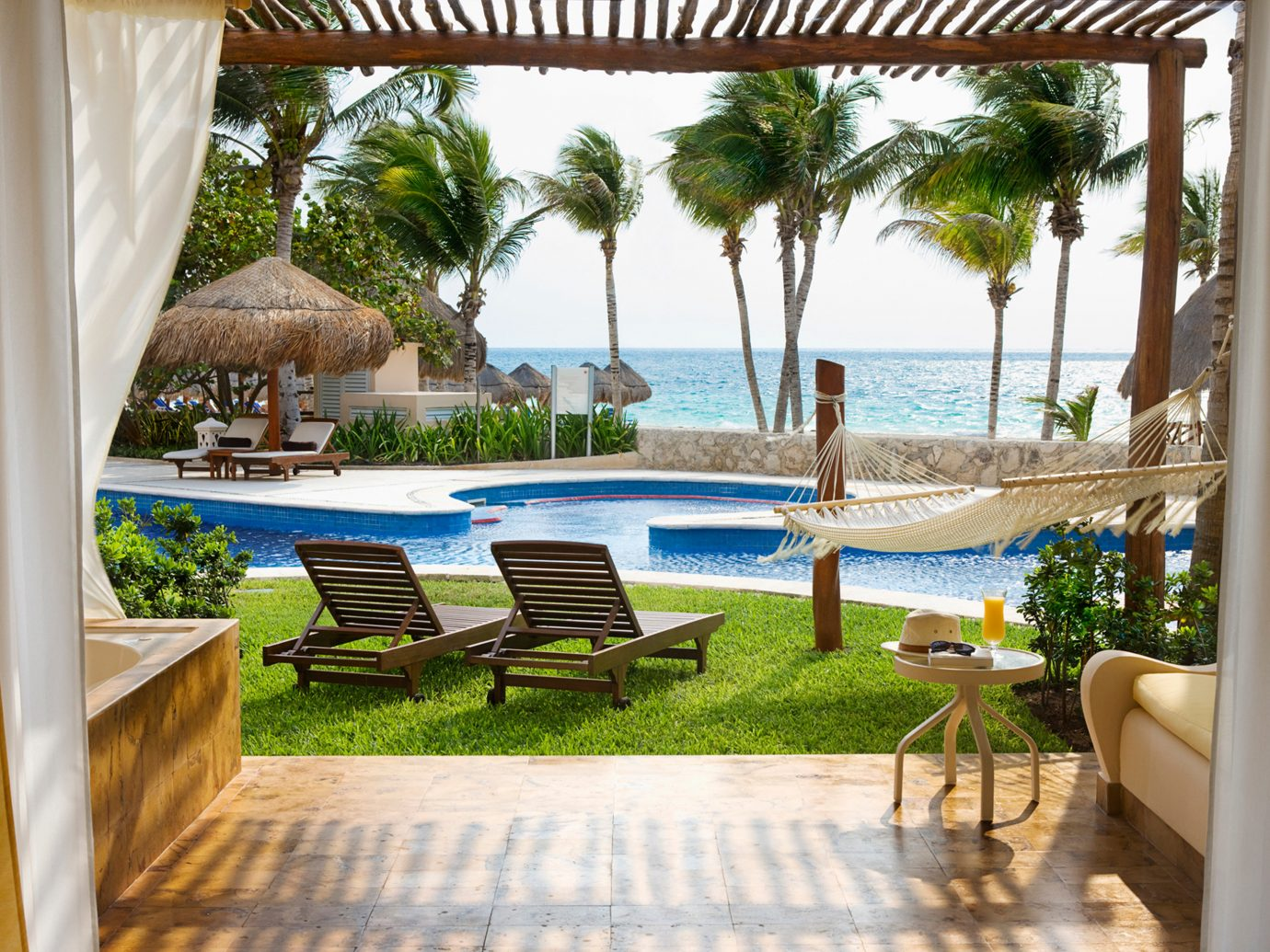 Beachfront Elegant Hip Hotels Luxury Modern Pool tree chair property leisure Resort estate building vacation Villa caribbean condominium home swimming pool furniture real estate mansion backyard porch hacienda eco hotel overlooking area Deck decorated