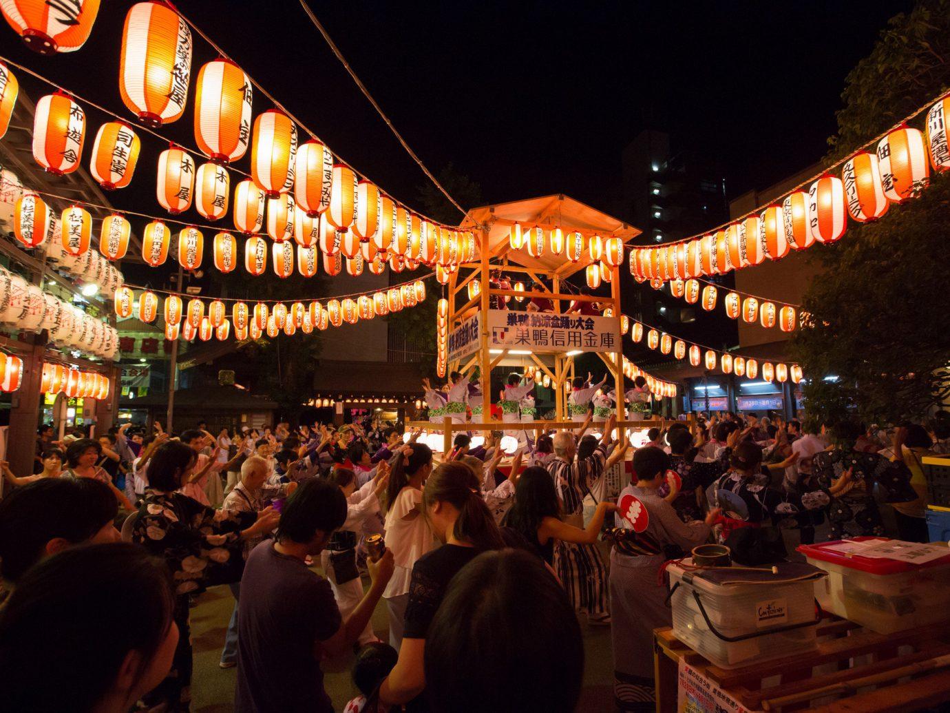 Arts + Culture Festivals + Events Travel Tips person crowd night people lighting festival City fête fun fair event evening