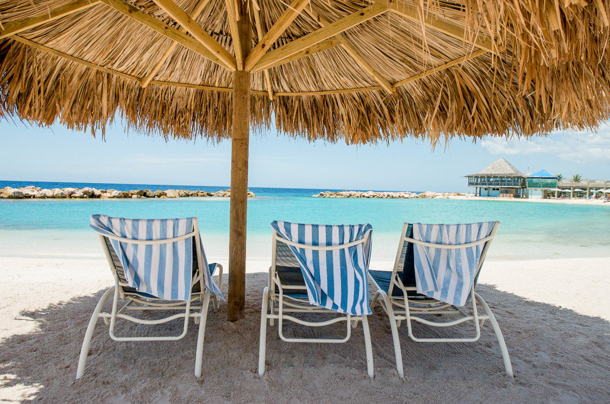 Boutique Hotels Romantic Getaways Romantic Hotels outdoor umbrella chair ground water Beach lawn Resort caribbean vacation Sea tropics outdoor furniture set real estate palm tree leisure arecales swimming pool Ocean table sunlounger resort town tourism sky estate Lagoon Deck empty lined shore sandy day dining table