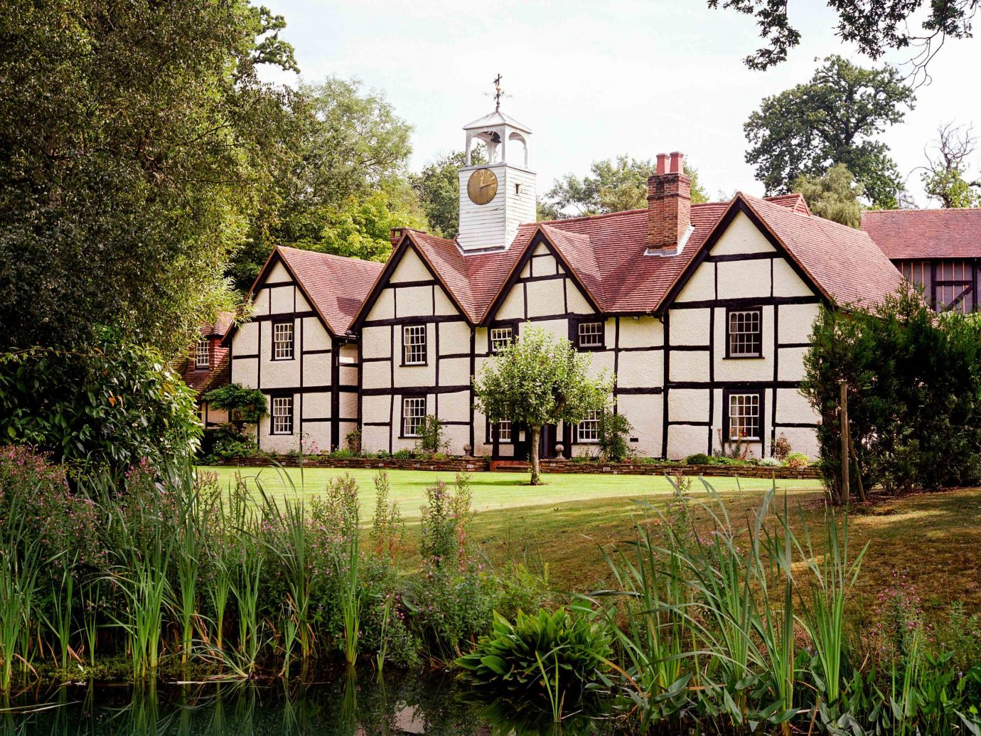 europe Trip Ideas waterway property reflection estate cottage house home water tree farmhouse real estate mansion manor house national trust for places of historic interest or natural beauty grass Village Canal watercourse bank landscape historic house plant pond facade Villa