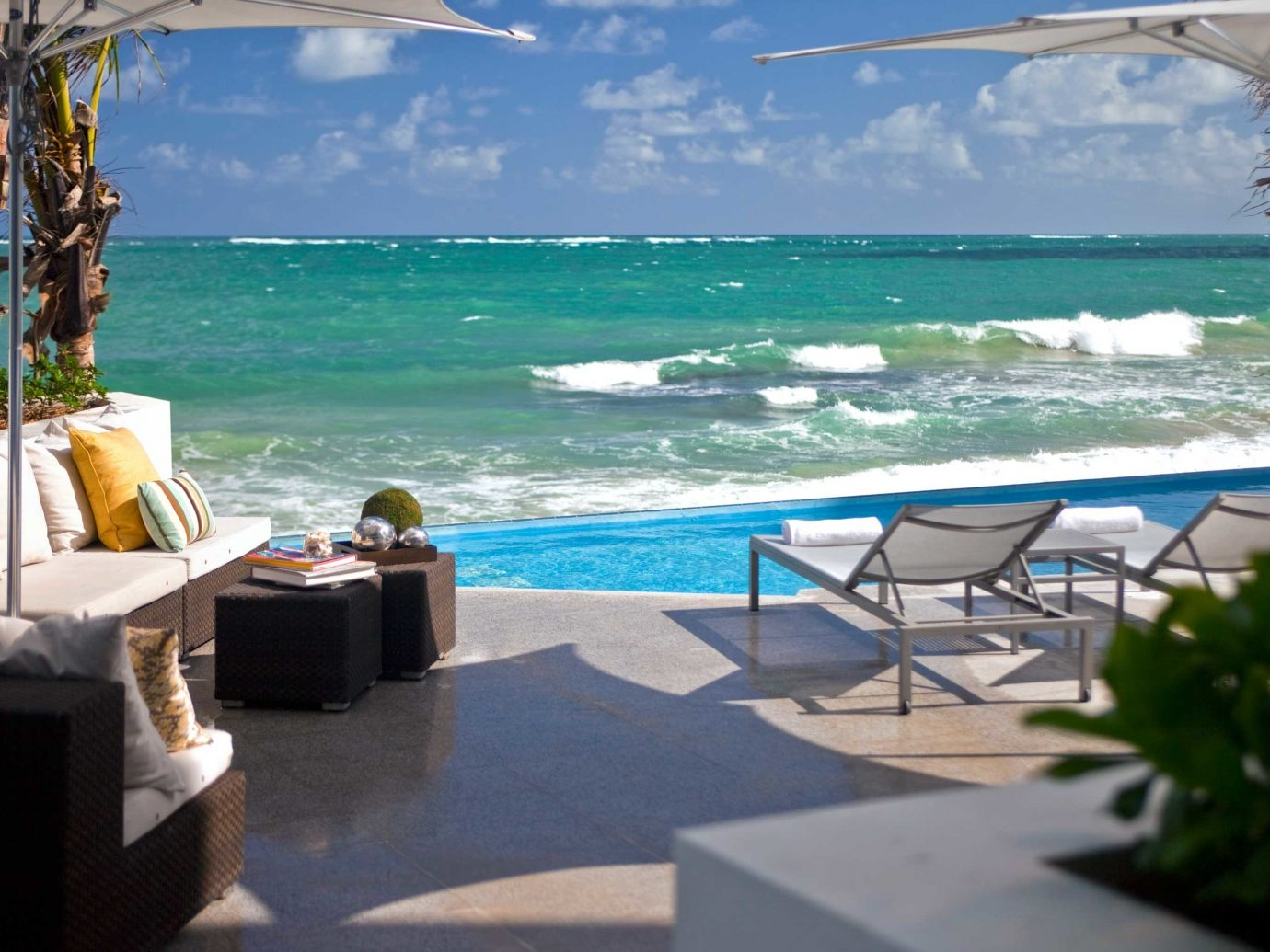 Beach Beachfront Hotels Living Patio Pool Resort Scenic views outdoor water leisure chair property caribbean vacation swimming pool Ocean Sea estate Villa bay shore day