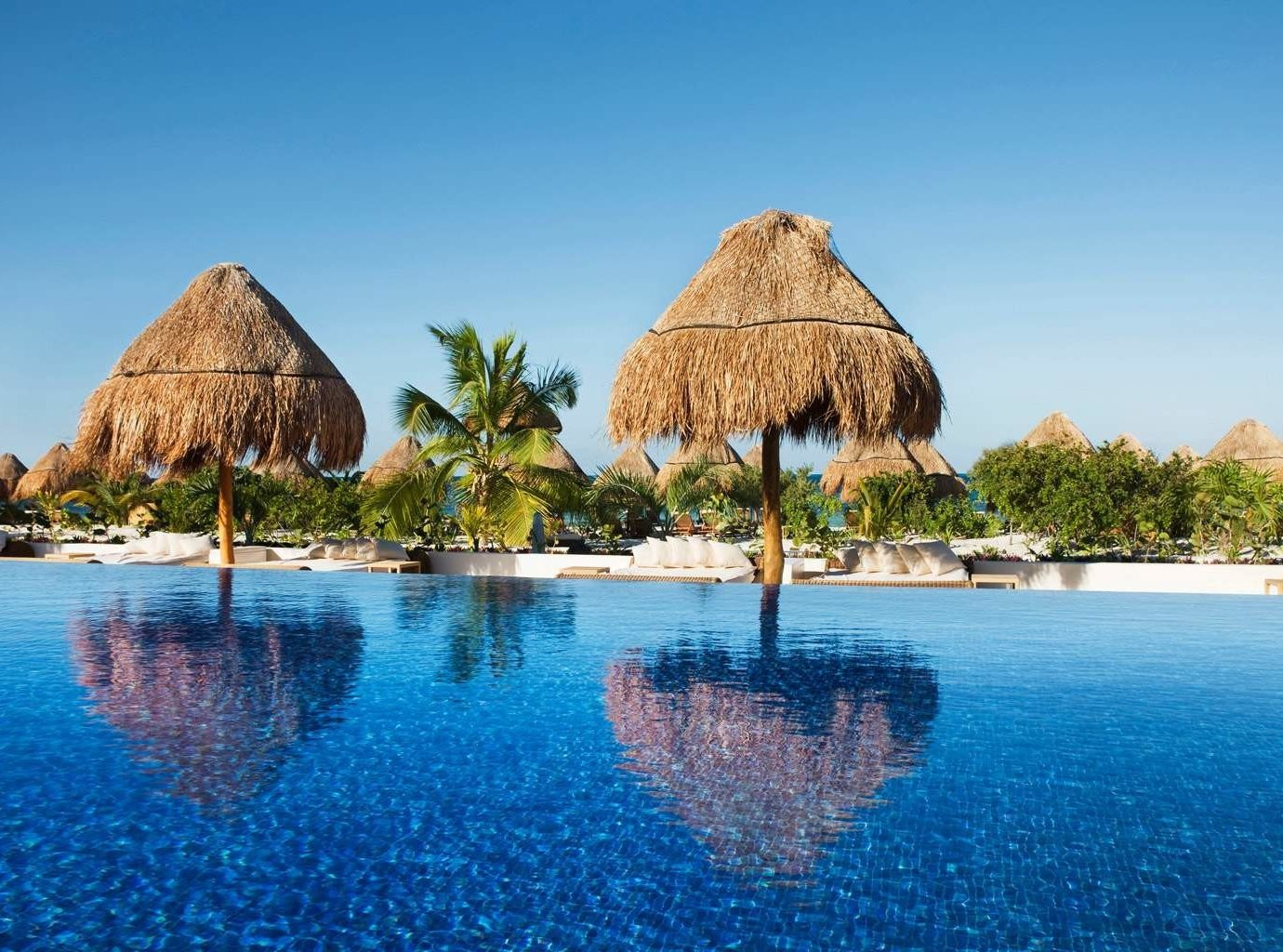 Hotels water outdoor sky Nature umbrella vacation lawn swimming pool Resort swimming Sea shore Lake Lagoon estate bay Beach Pool day empty surrounded Island