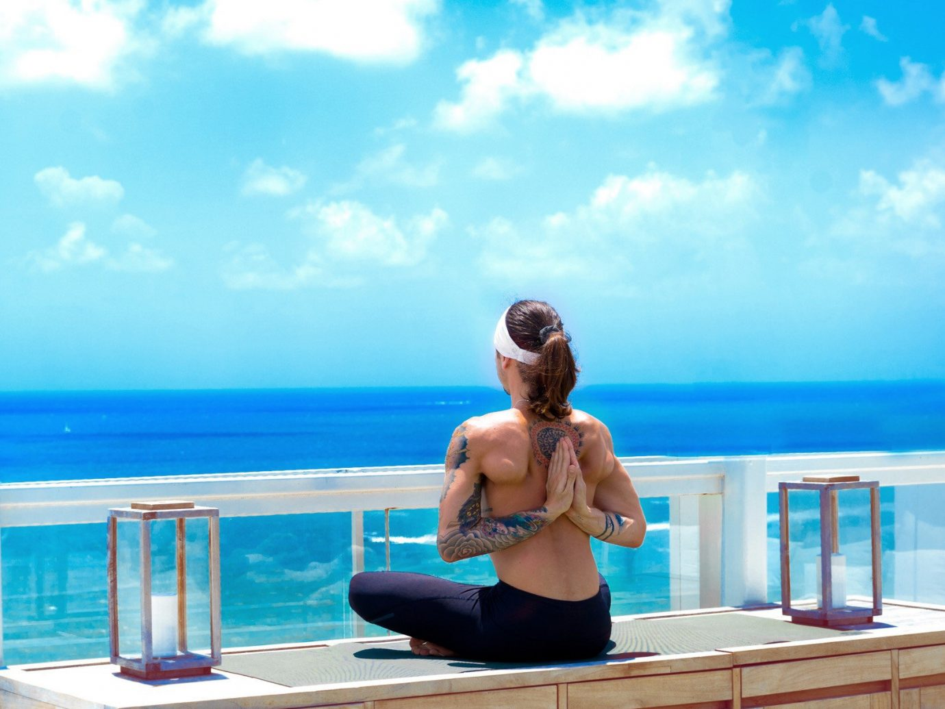 Health + Wellness Hotels Yoga Retreats sky outdoor human action leisure human positions sitting blue swimming pool vacation physical fitness sun tanning leg Sea sports shore