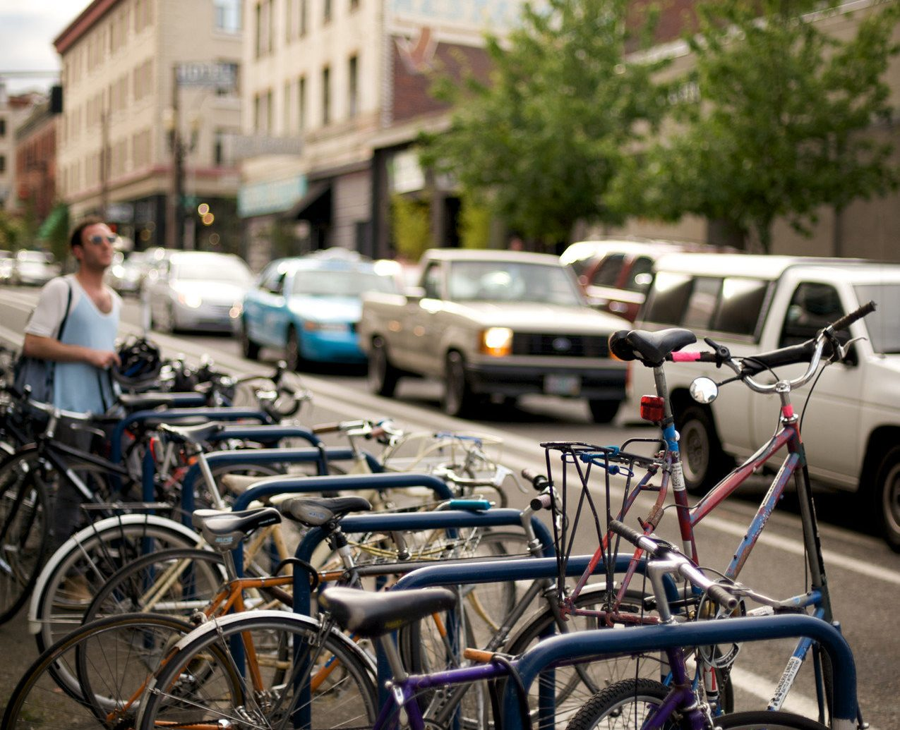 Bikes Biking Buildings cars city streets Offbeat people Roads streets trees Trip Ideas urban bicycle outdoor building cycling parked vehicle lane urban area sidewalk human settlement street sports equipment tourism road cycling rack bicycle rack