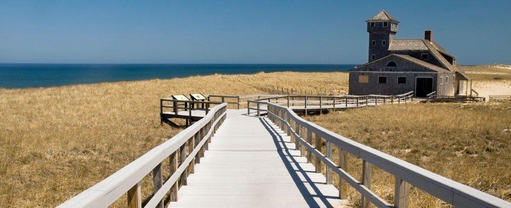 Jetsetter Guides Fence sky outdoor grass Coast tower walkway Ocean Sea boardwalk wooden railing pier lighthouse overlooking
