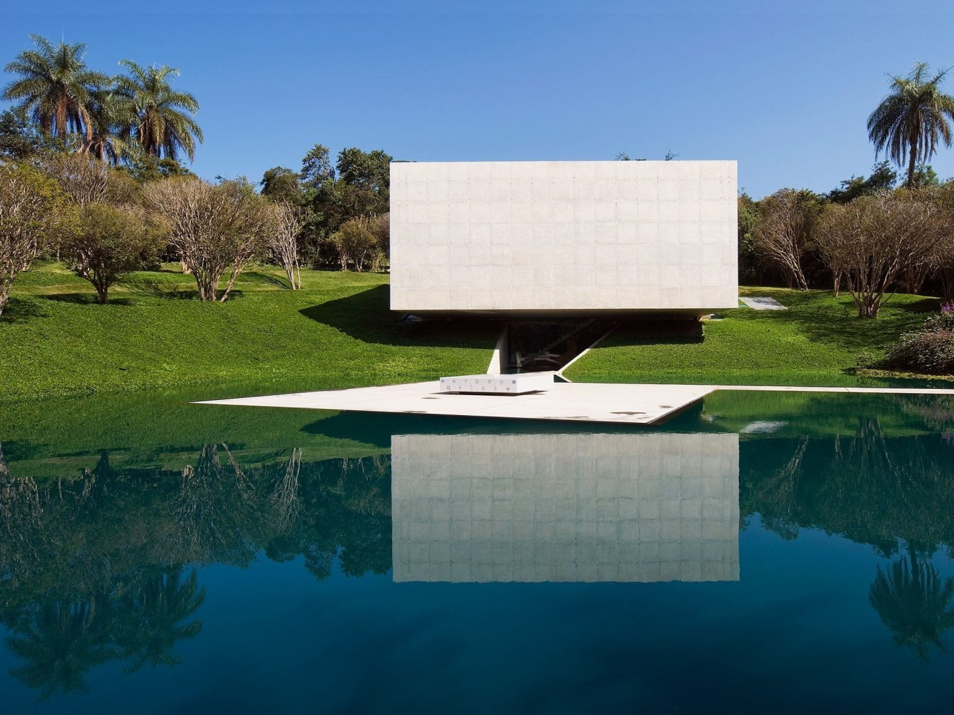 Arts + Culture tree sky grass outdoor structure estate swimming pool house sport venue home Nature lawn landscape architect golf club backyard Lake reflection golf course Garden pond