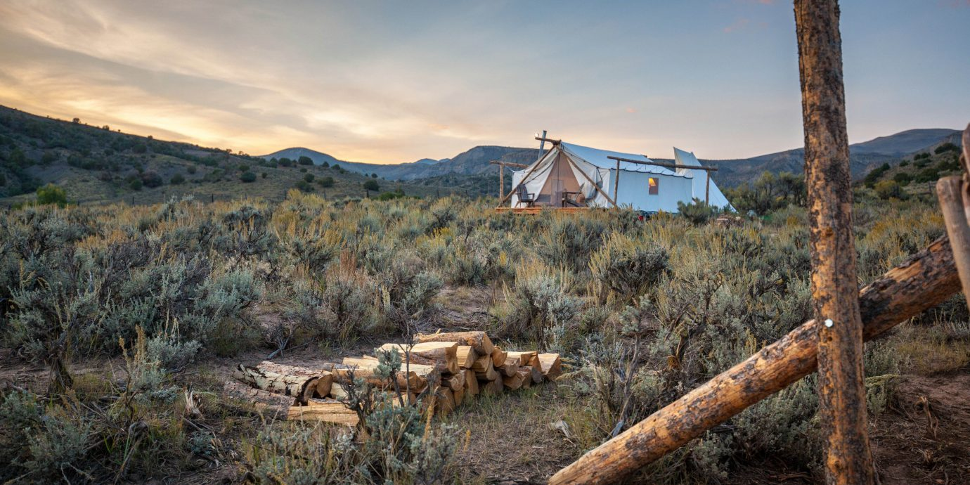 Glamping Hotels Outdoors + Adventure Trip Ideas Weekend Getaways outdoor sky grass mountain Nature mountainous landforms wilderness tree natural environment rural area landscape dry hillside