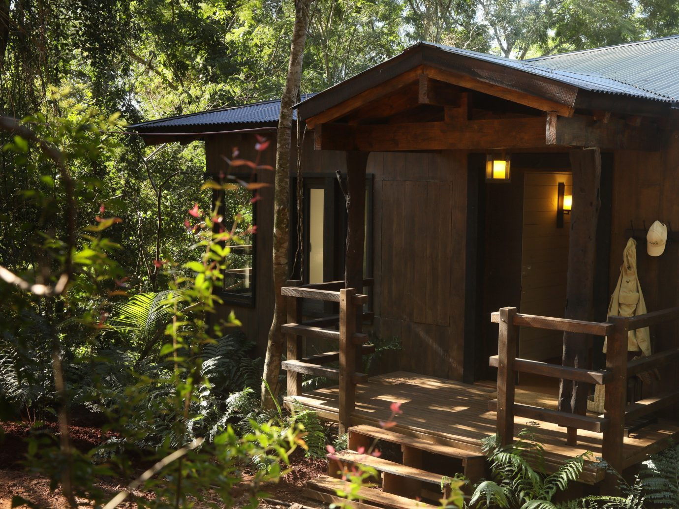 Hotels Outdoors + Adventure tree outdoor building cottage log cabin house shed hut home shack outdoor structure plant real estate backyard landscape porch Garden