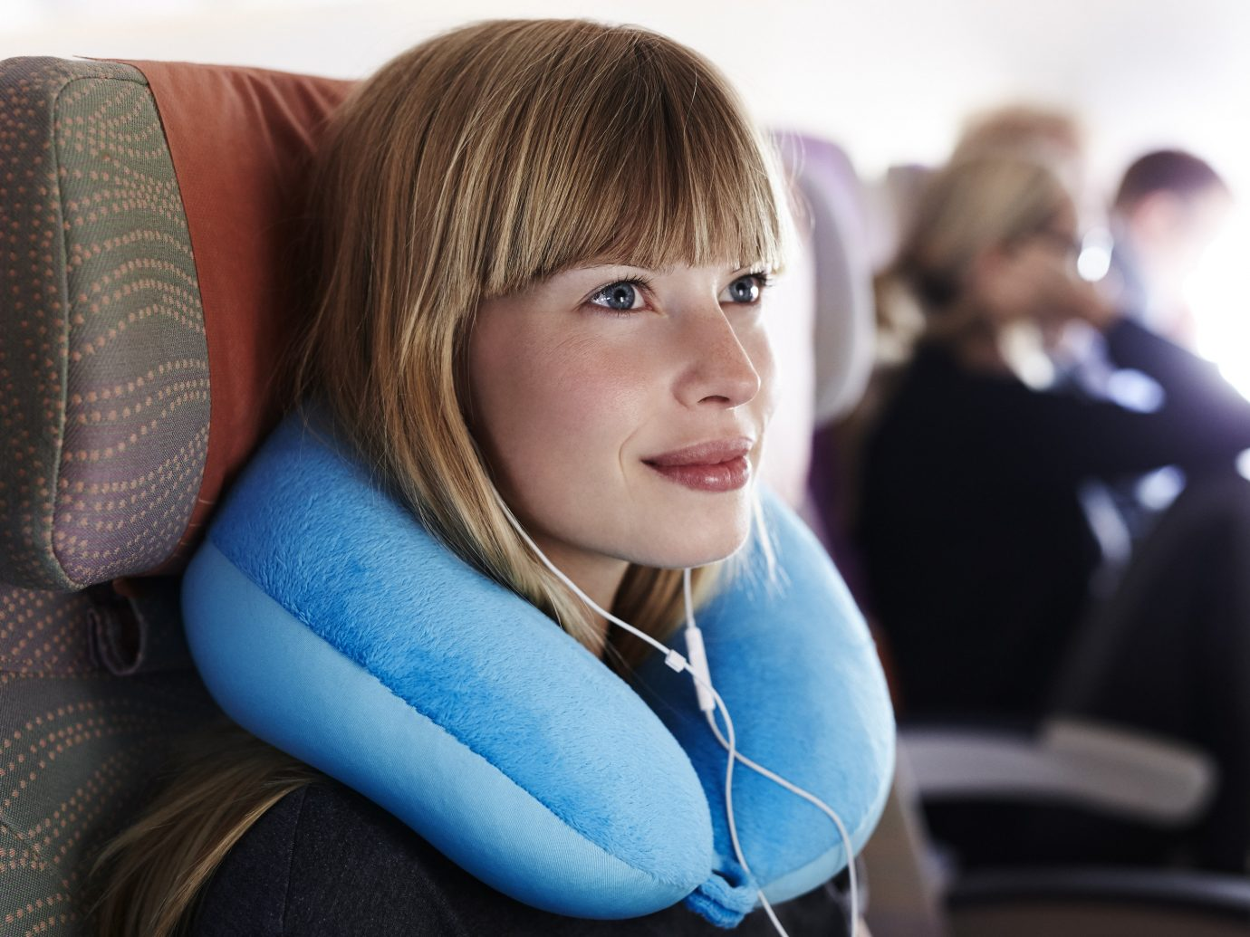 Girl wearing a neck pillow on a plane