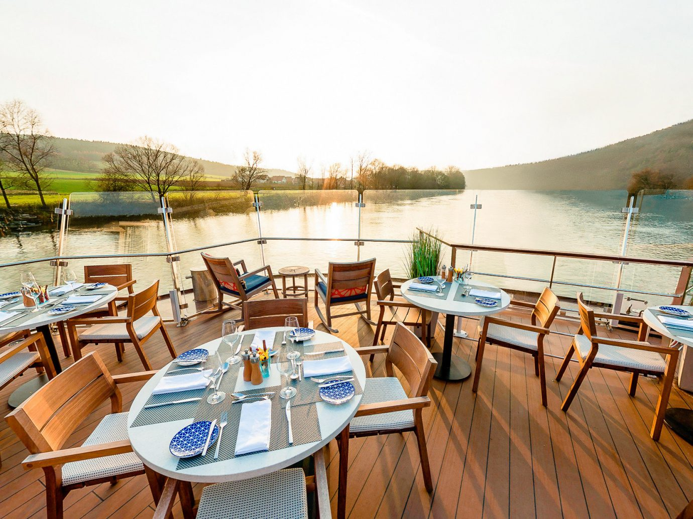 Cruise Travel Luxury Travel chair table sky water wooden Deck overlooking Boat real estate Resort dock leisure restaurant outdoor structure vacation yacht recreation furniture