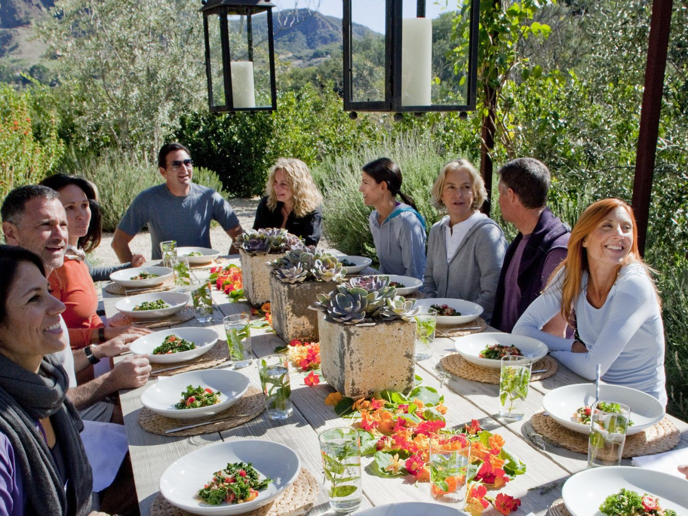 Health + Wellness Hotels Yoga Retreats person tree outdoor table food group people plate meal lunch supper Picnic brunch sense dinner dish restaurant cuisine day dining table