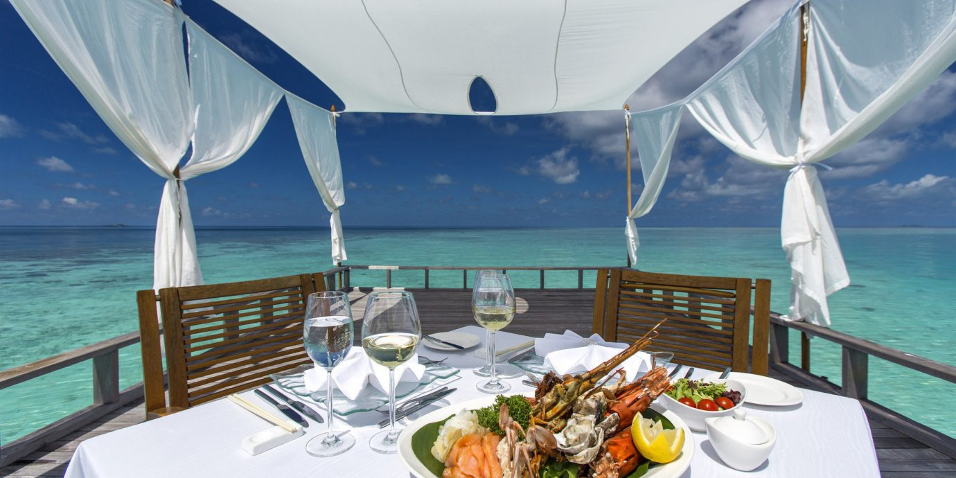 cabana calm clear water Dining Eat fine dining food Food + Drink gourmet isolation Luxury Ocean ocean view outdoor dining private private dining remote serene table setting turquoise view Boat vehicle passenger ship outdoor ship luxury yacht ecosystem yacht watercraft caribbean tent outdoor object