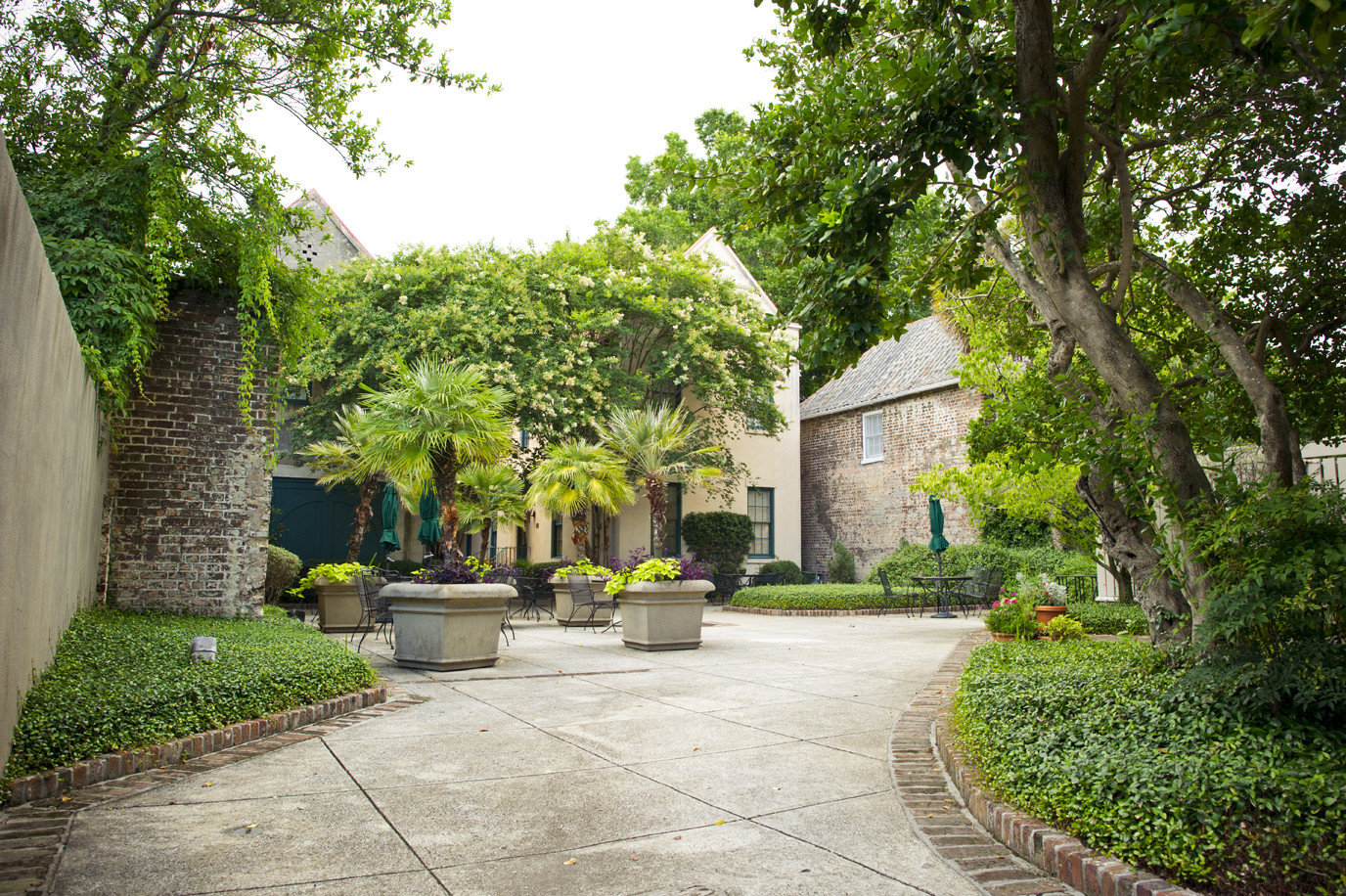 Hotels tree outdoor ground grass property Garden estate Architecture Courtyard real estate leaf walkway arecales plant sidewalk home park hacienda landscape house palm tree Villa plantation outdoor structure landscaping shrub yard mansion stone cement concrete curb