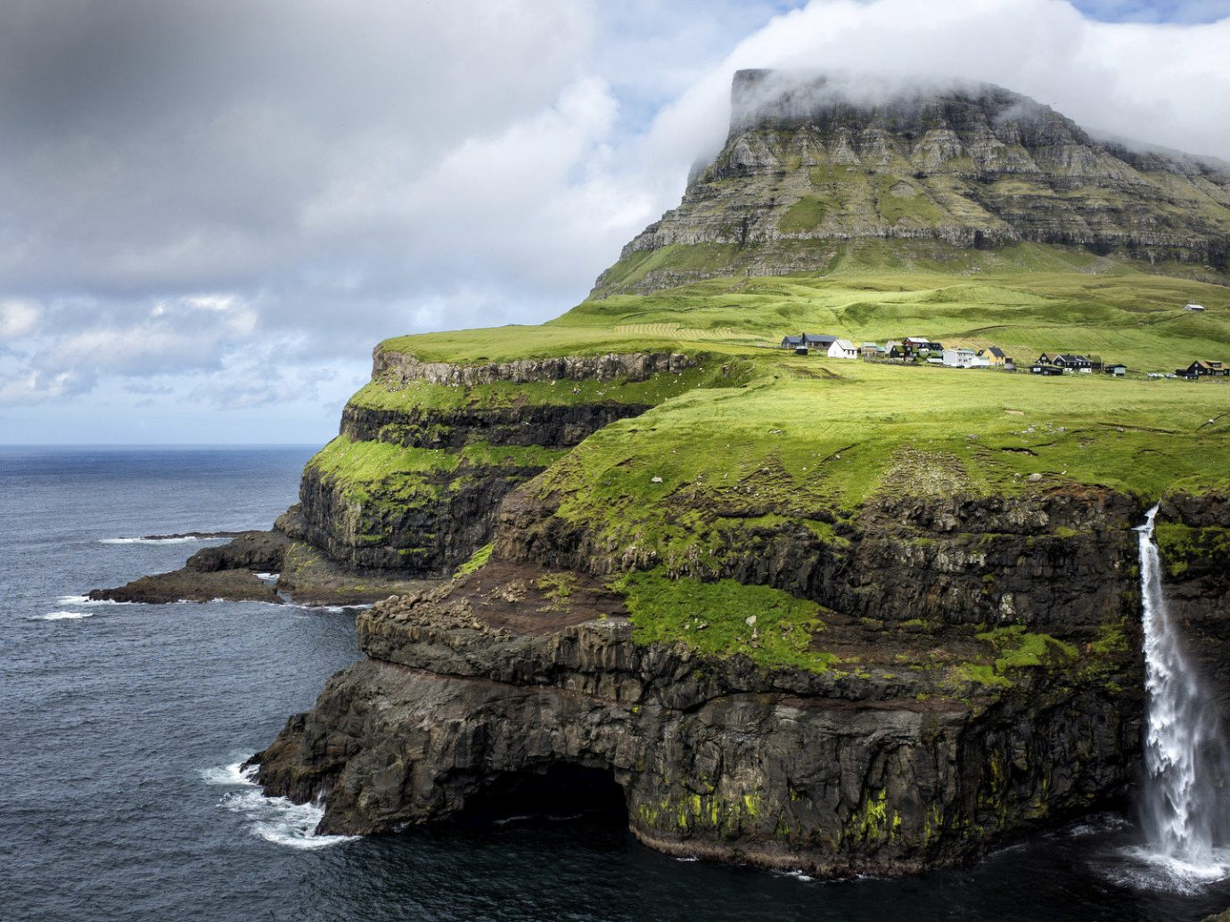 Faroe Islands Japan Jordan Michigan Montenegro Offbeat Oregon Patagonia Travel Tips Trip Ideas Nature sky outdoor mountain water rock Waterfall geographical feature landform Coast body of water cliff Sea Ocean terrain islet landscape cape Island bay fjord cove hillside