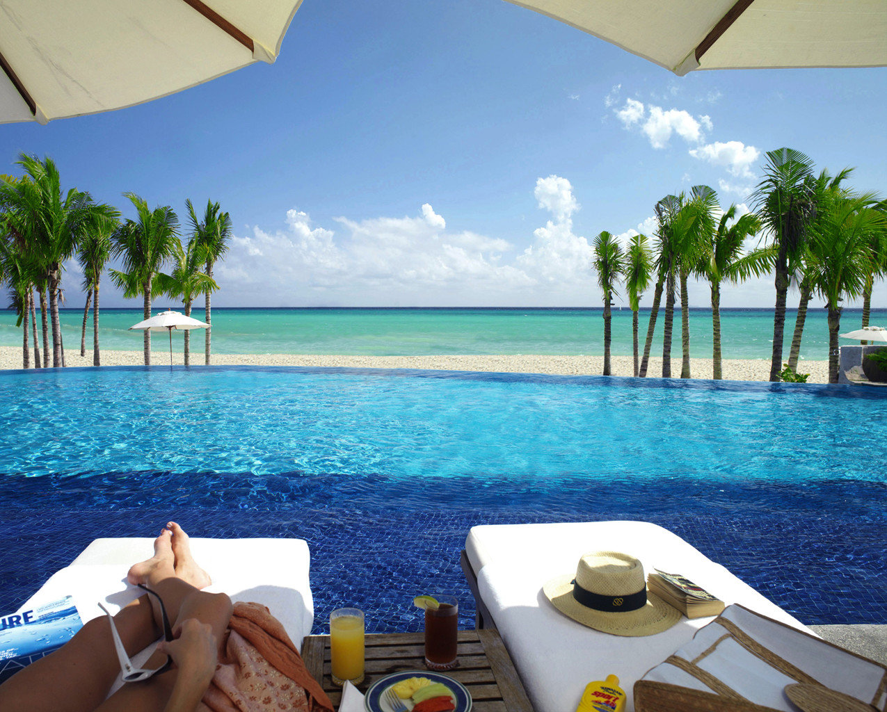 All-Inclusive Resorts Beachfront Hotels Living Lounge Luxury Travel Ocean Pool Romance Trip Ideas Tropical water sky table leisure outdoor caribbean vacation swimming pool Sea Resort Beach Lagoon bay estate Deck Island Villa cape shore
