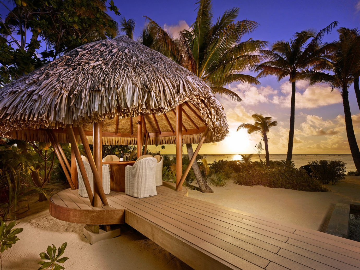 Beach Dining golden hour Hotels isolation majestic Ocean outdoor dining private private dining remote Romance Romantic serene Sunset Tropical white sands tree Resort vacation estate arecales Villa plant palm hut furniture decorated