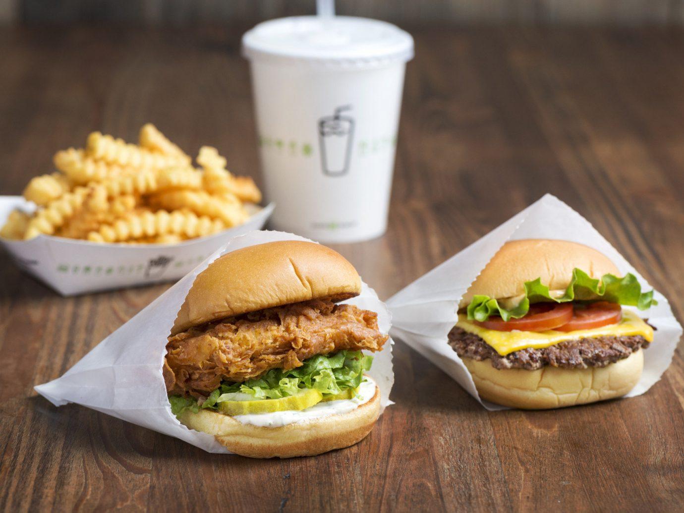 Food + Drink table food dish cup hamburger veggie burger meal slider fast food breakfast produce sandwich wooden snack food cuisine vegetable meat cheeseburger