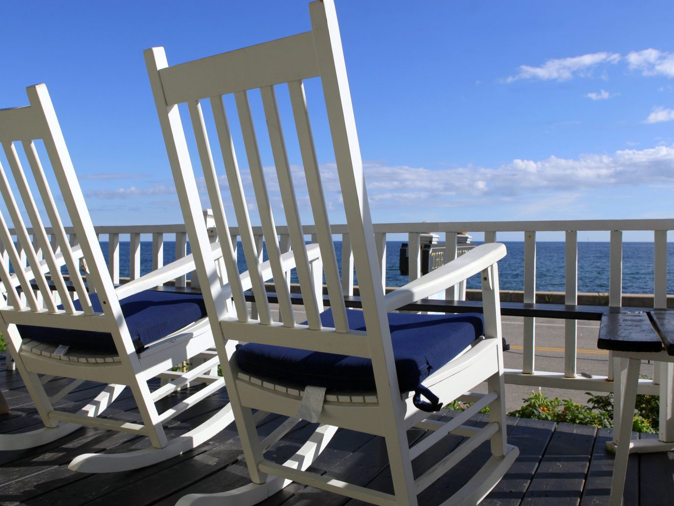 Balcony Beachfront Country Hotels Inn Patio Scenic views Waterfront chair floor property condominium marina dock Dining white headquarters lawn Resort apartment porch area overlooking set Deck furniture dining table