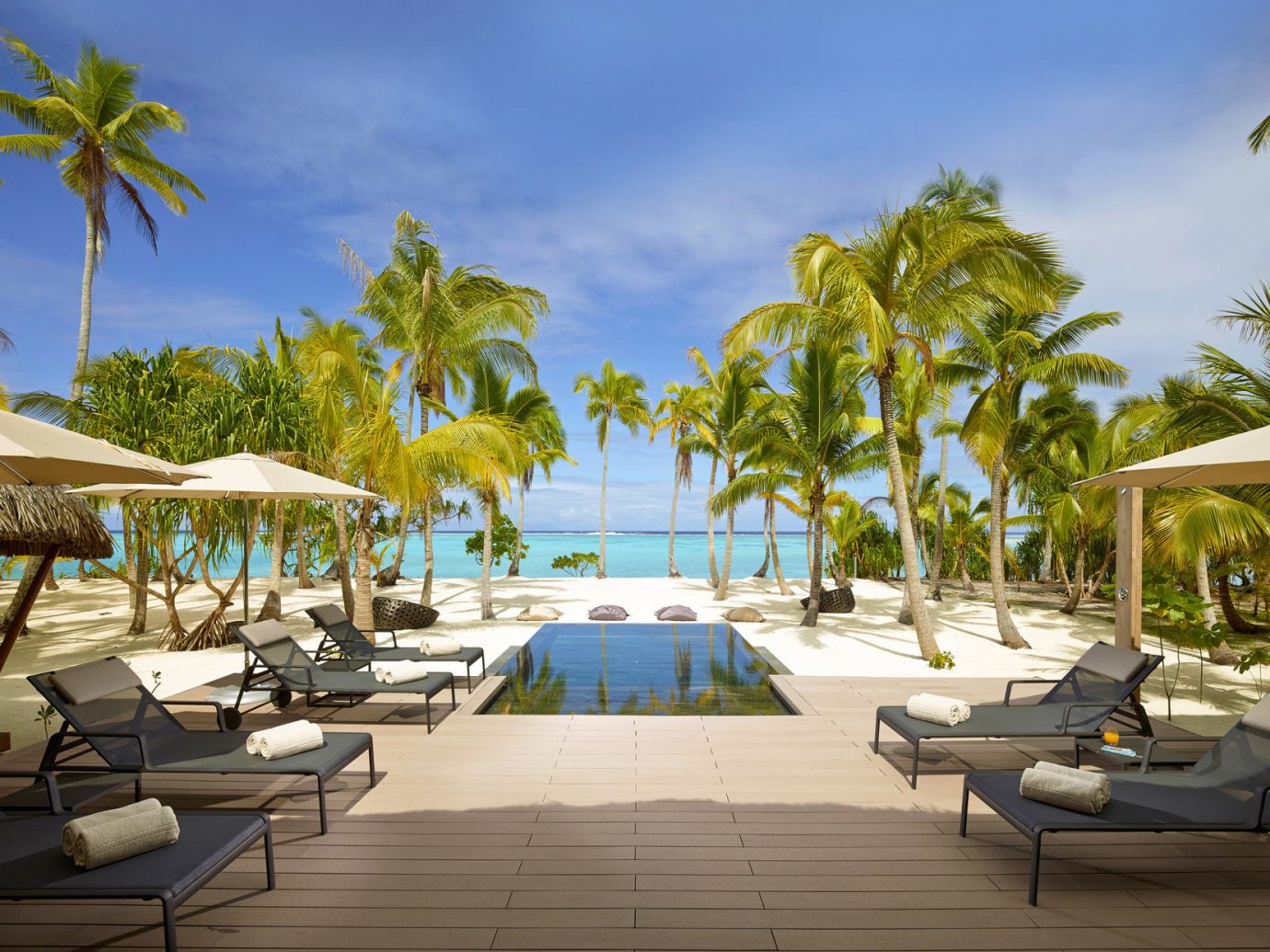 All-Inclusive Resorts Beach Boutique Hotels calm canopy Family Travel Hotels lounge chairs Luxury Luxury Travel Ocean outdoor pool palm trees Pool reflection remote Romance Romantic Hotels serene Tropical turquoise tree outdoor umbrella palm leisure Resort property vacation estate swimming pool caribbean arecales Villa walkway lined Deck furniture shade several day sandy