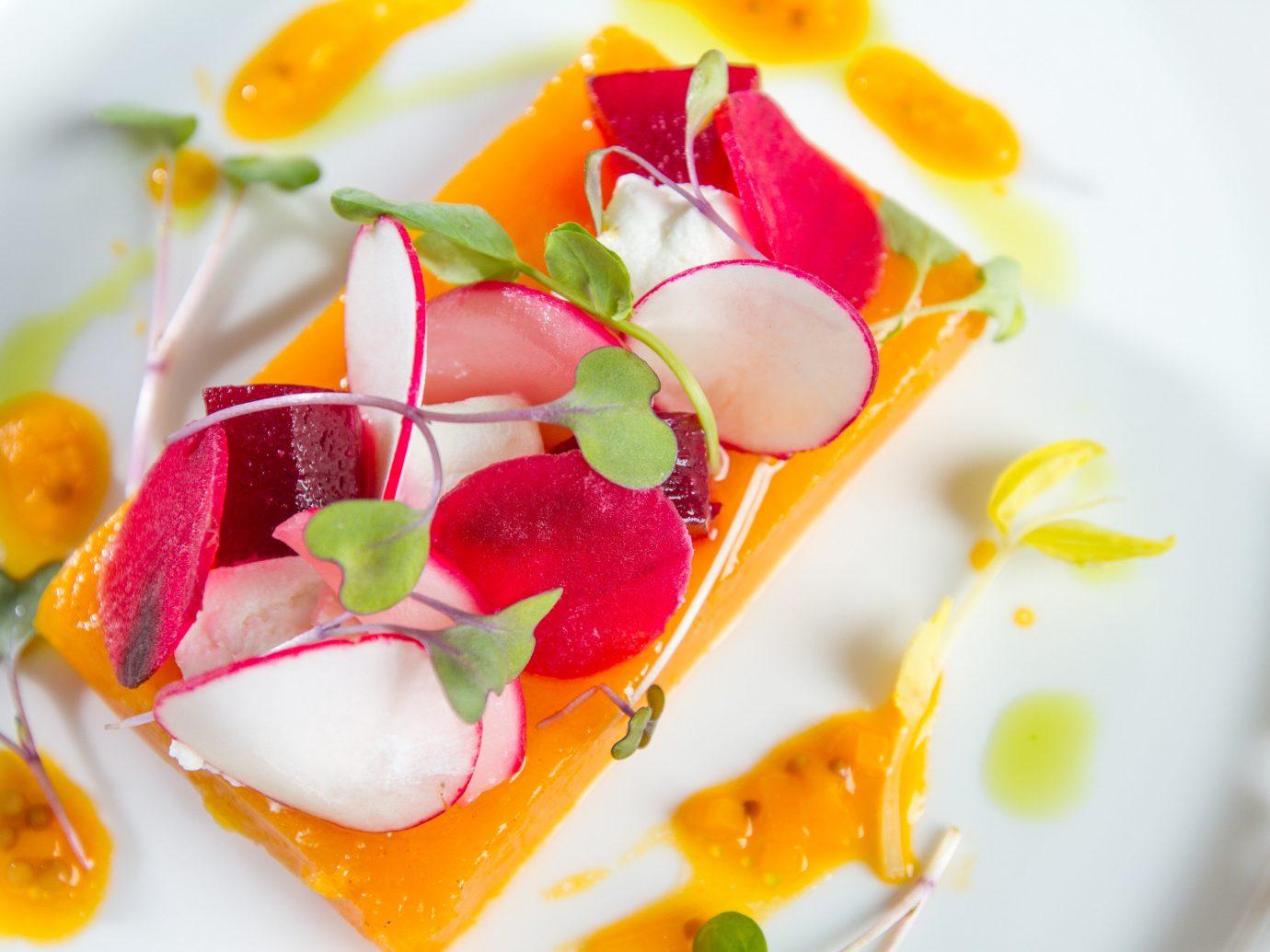 Jetsetter Guides plate food dish plant produce fruit petal flower dessert land plant cuisine flowering plant sweetness slice sauce flavor containing arranged
