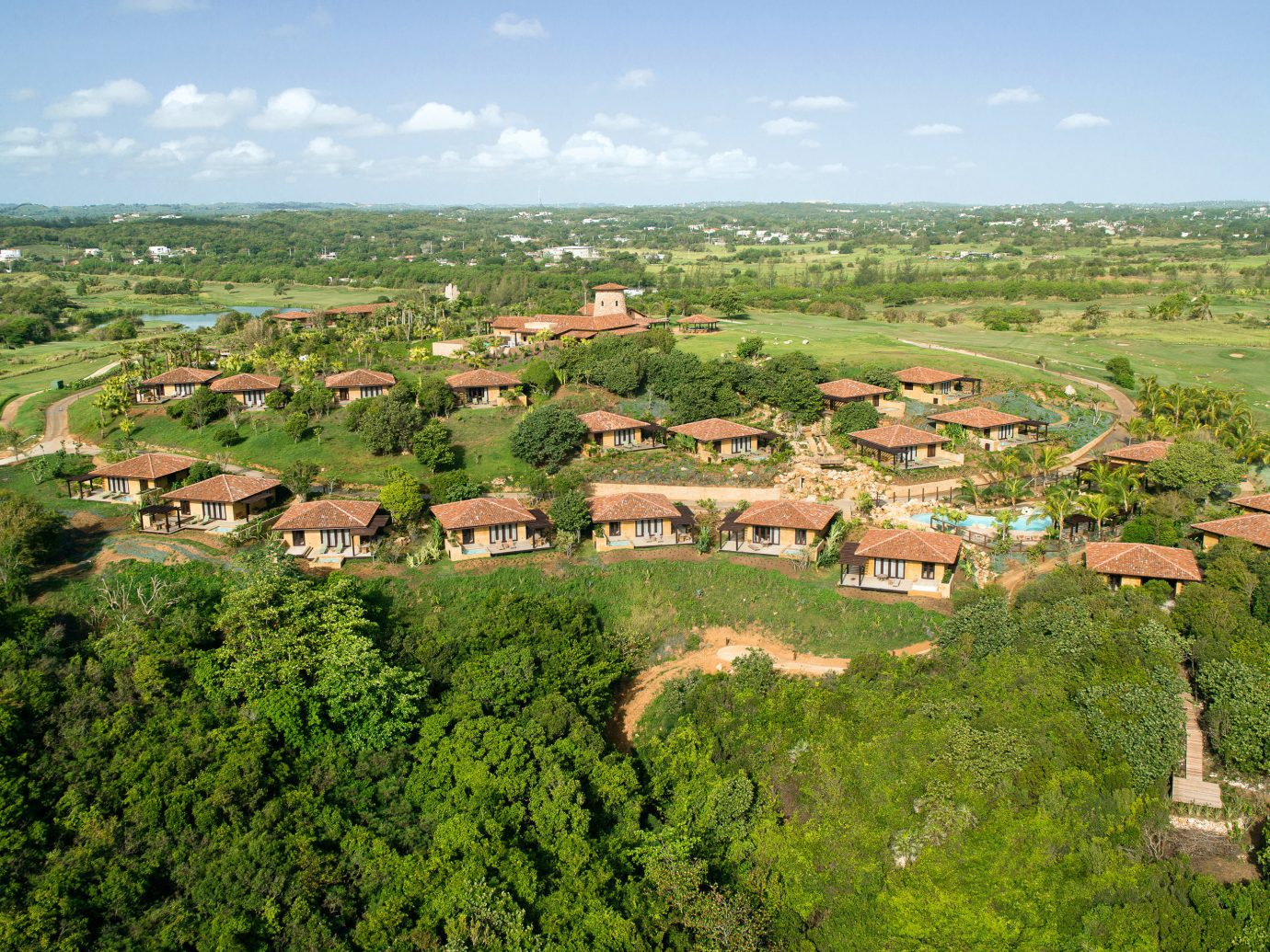 Hotels sky grass outdoor aerial photography geographical feature mountain Town tree ecosystem bird's eye view Nature hill plain human settlement Village residential area field rural area estate landscape plateau meadow terrain panorama overlooking lush Garden hillside day highland