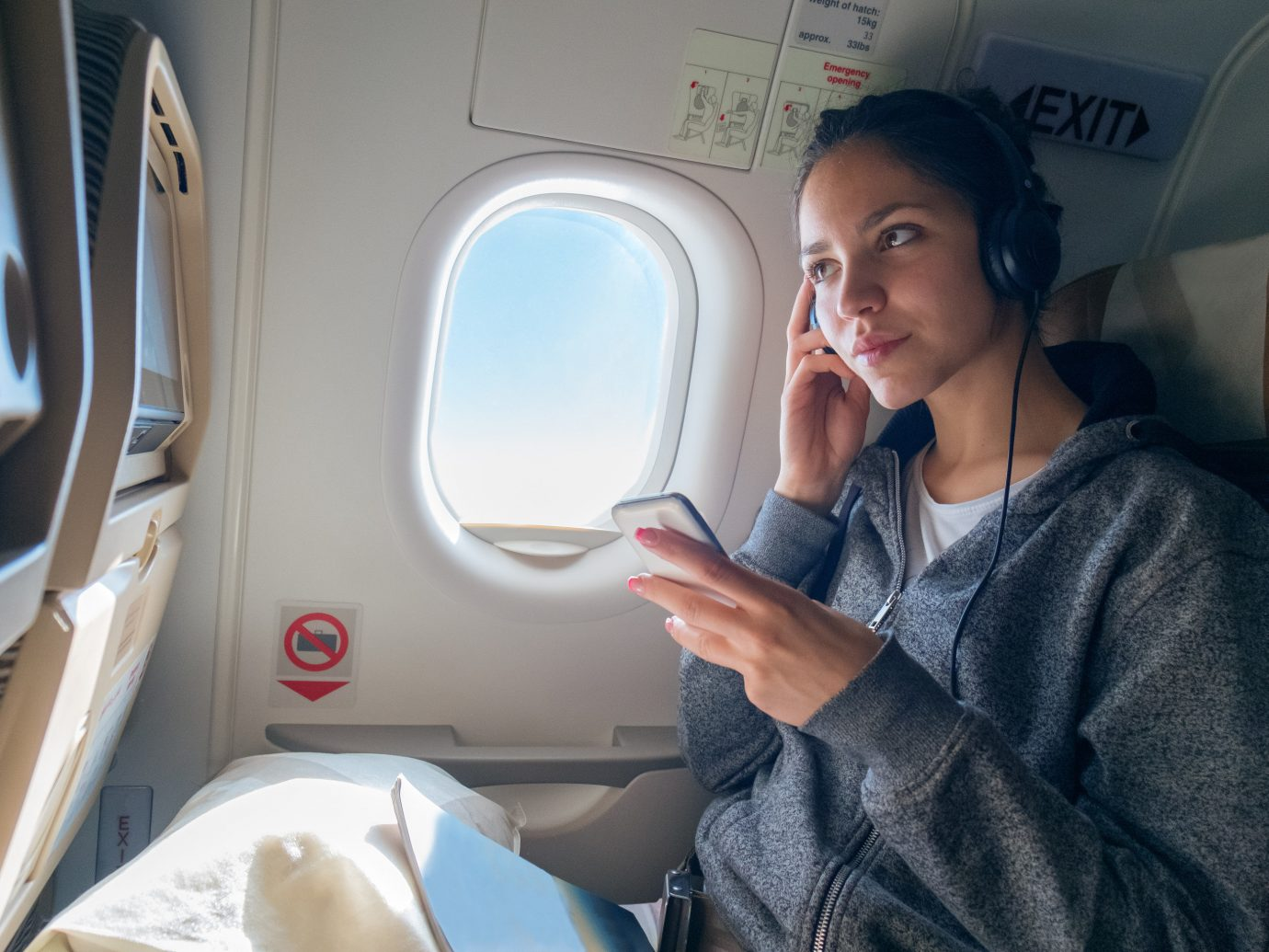 Girl listening to a phone on a plane