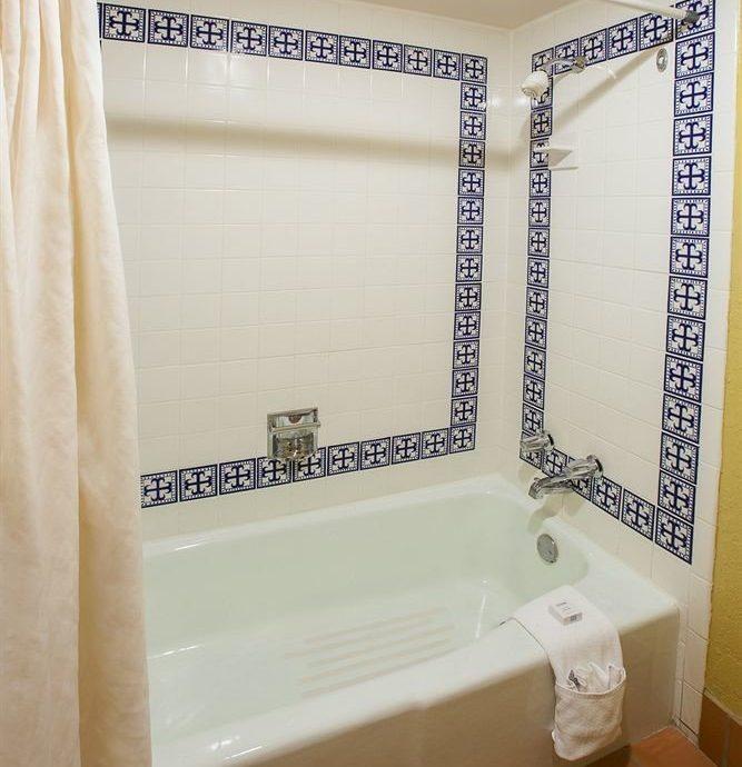bathroom plumbing fixture bathtub white curtain tiled tile Bath