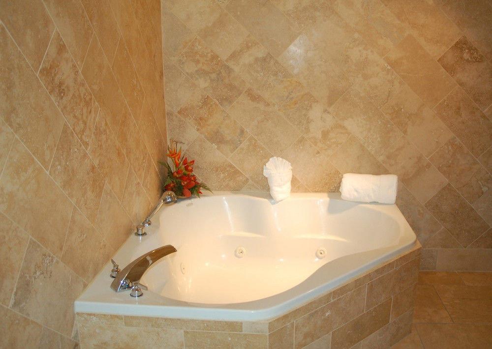 bathroom vessel bathtub swimming pool plumbing fixture flooring bidet jacuzzi white tile tan tiled