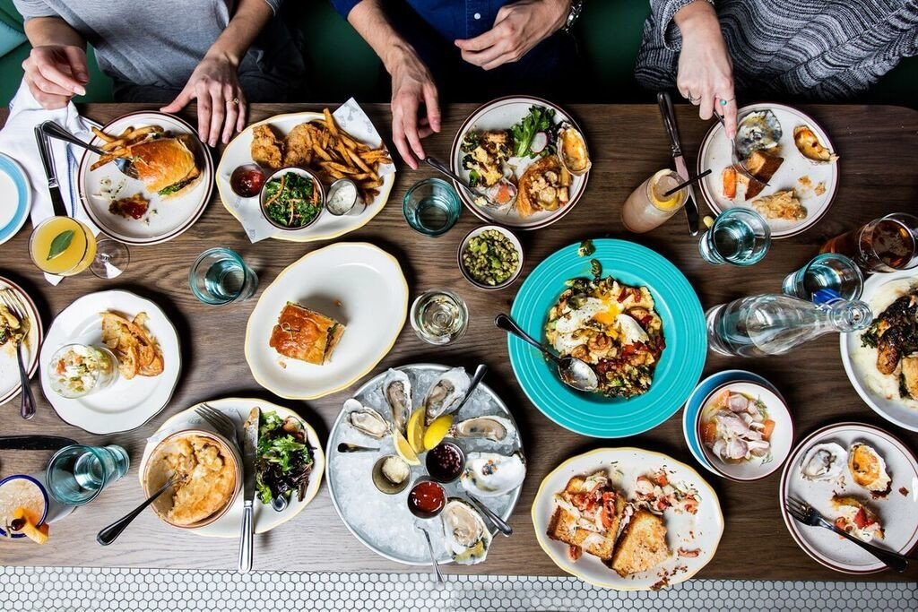 aerial Dining Eat food Food + Drink hands oysters people plates Seafood table Trip Ideas person plate dish group meal many bunch cuisine several lunch different