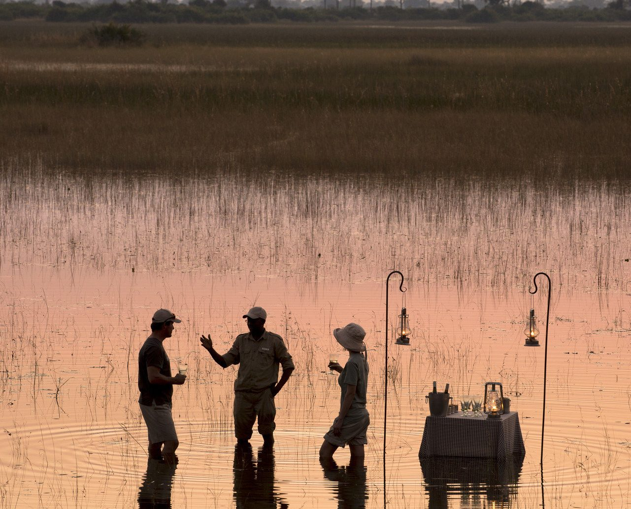 calm fisherman fishing golden hour grass Lake Luxury Nature Outdoor Activities outdoor dining Outdoors people reflection remote River Safari serene silhouette sunrise Sunset Trip Ideas outdoor atmospheric phenomenon natural environment morning dawn wetland evening