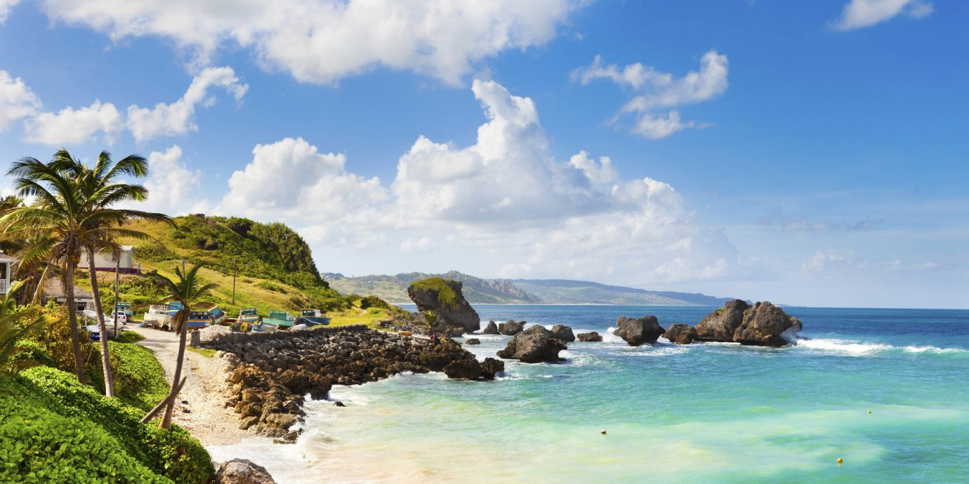 Hotels News Trip Ideas sky outdoor water Beach Coast shore Sea Nature Ocean body of water landform geographical feature rock vacation caribbean cloud bay cove islet tropics cape wave cliff Island terrain day sandy
