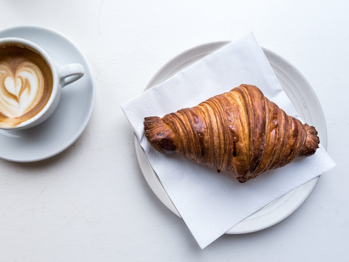 Copenhagen Denmark Trip Ideas table cup coffee plate pain au chocolat piece croissant danish pastry pastry food baked goods breakfast slice flavor dessert