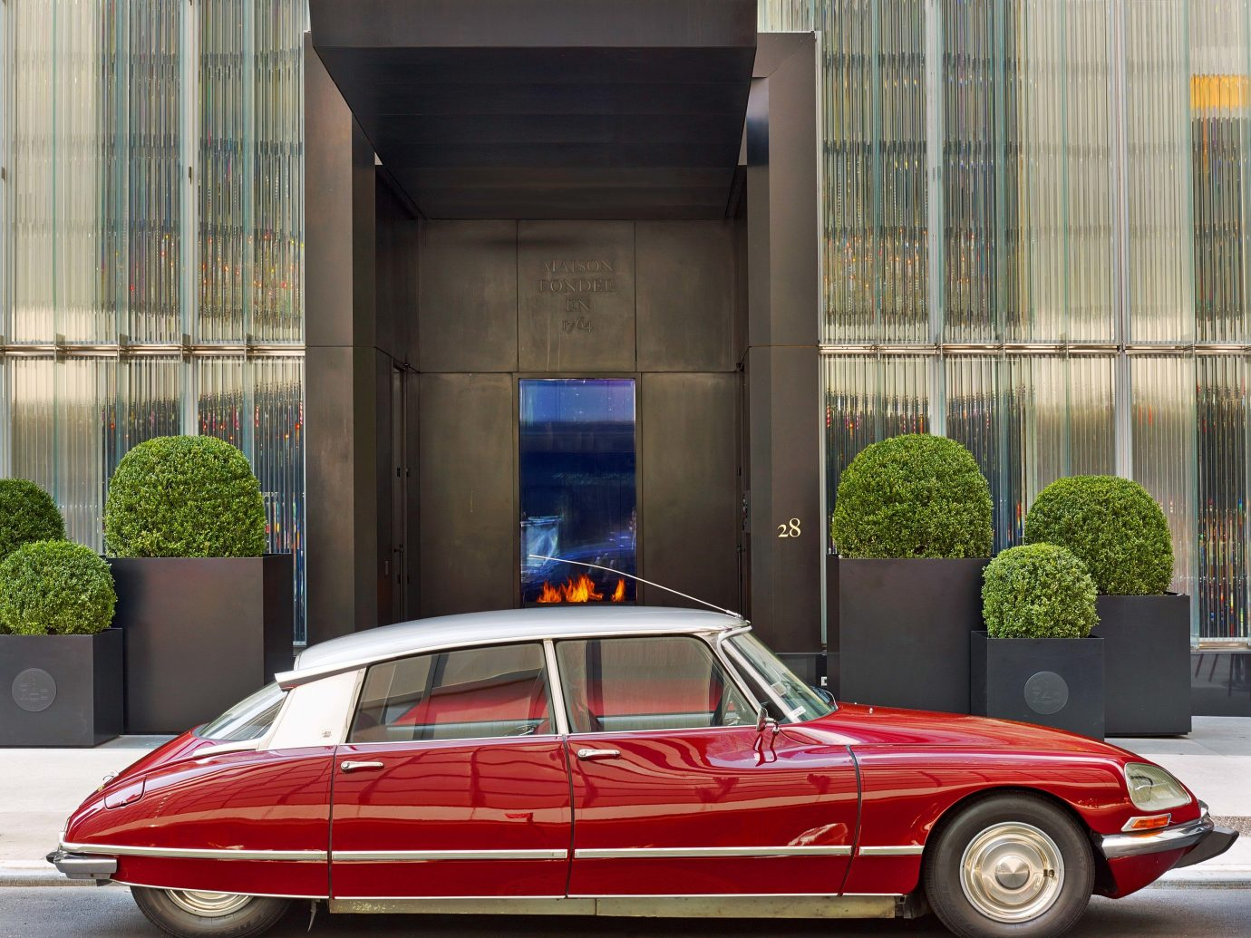Baccarat Hotel & Residences, Best Hotels in NYC, Offbeat building outdoor car vehicle land vehicle red luxury vehicle automotive design automobile make automotive exterior parked sedan performance car antique car Classic vintage car curb