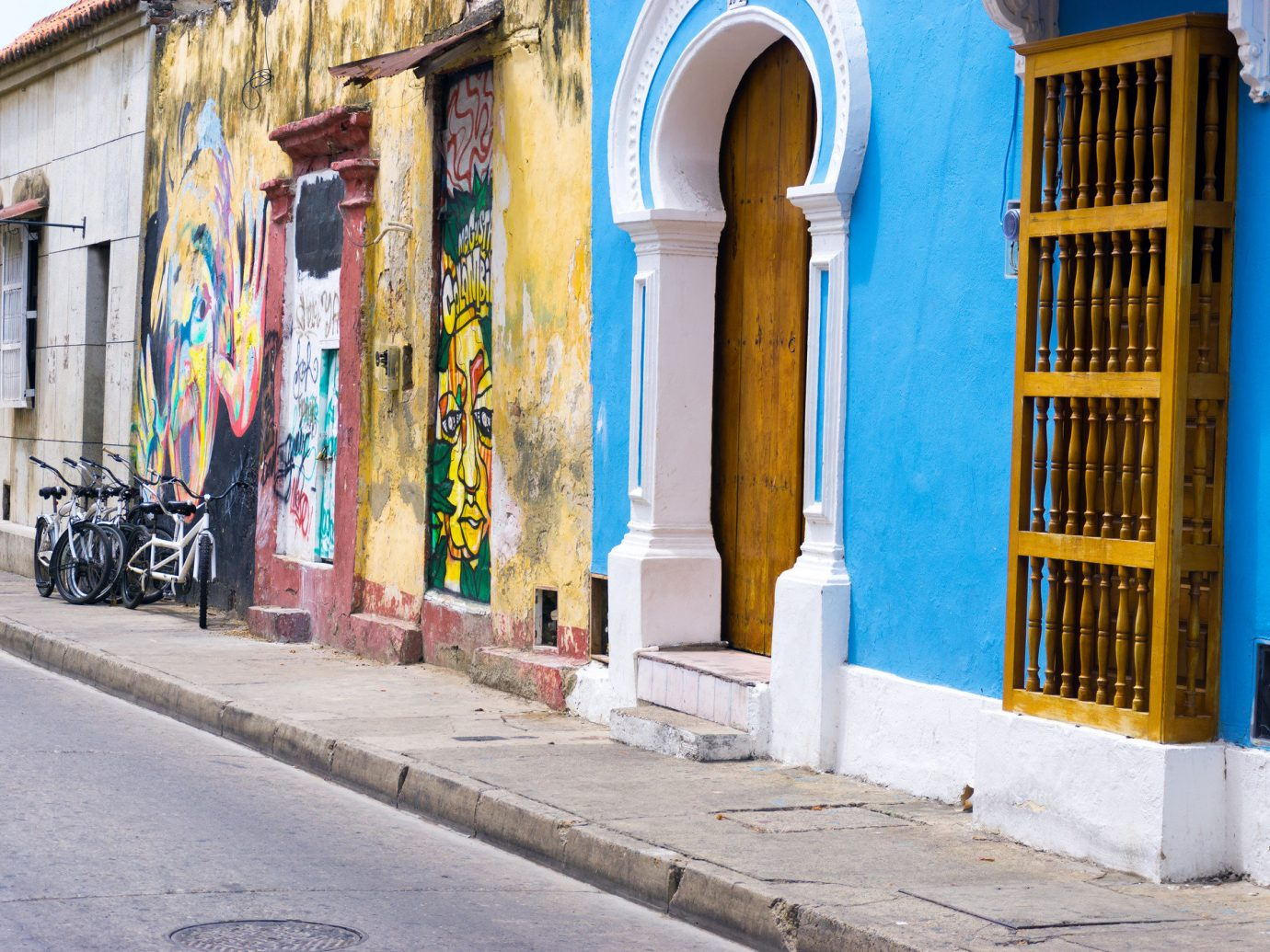 Offbeat building outdoor color road blue street Town urban area neighbourhood way City wall Architecture sidewalk scene facade art alley infrastructure ancient history past scooter curb