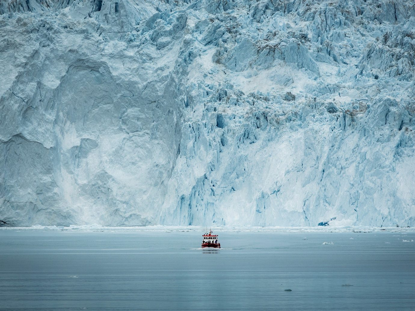 A small passenger boat crosses the Eqip glacier