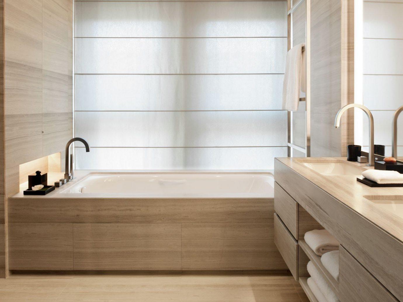 Hotels indoor room bathroom floor plumbing fixture sink cabinetry hardwood bathtub interior design flooring countertop wood tile furniture Design wood flooring bathroom cabinet