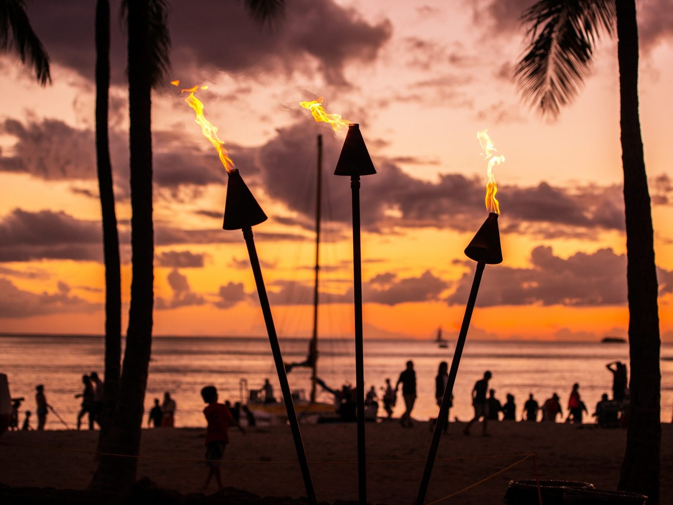 Beach Jetsetter Guides Ocean Scenic views Sunset sky outdoor water cloud Sun evening dusk morning afterglow dawn sunlight sunrise Sea silhouette tree setting clouds sailing vessel shore sandy