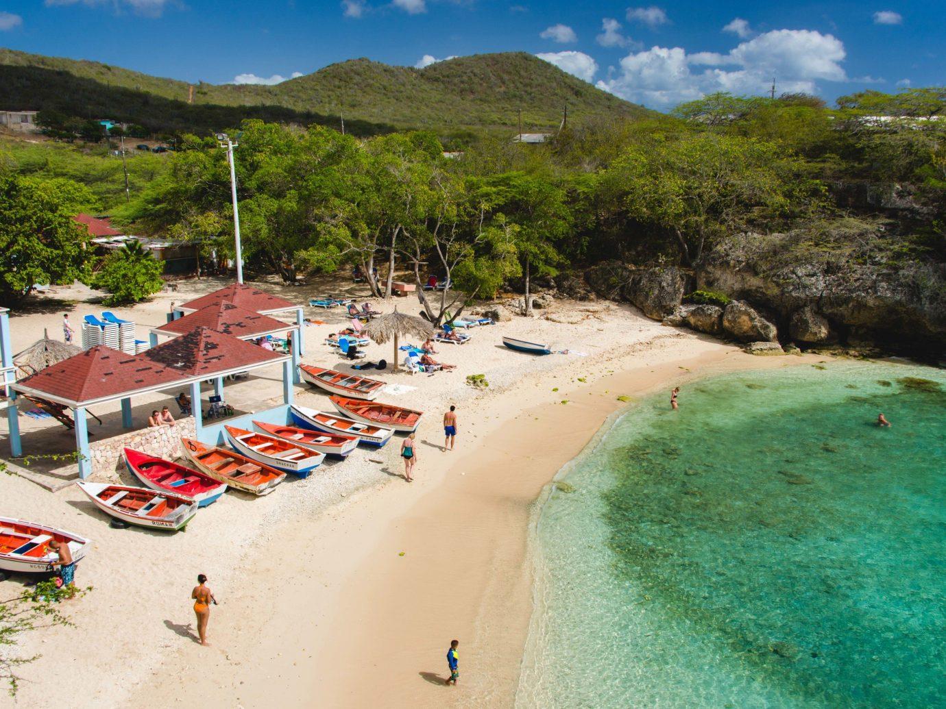 Beaches Beach body of water Coast coastal and oceanic landforms Sea Resort tourism shore bay sky caribbean leisure water vacation cove tropics terrain tree inlet sand landscape Lagoon