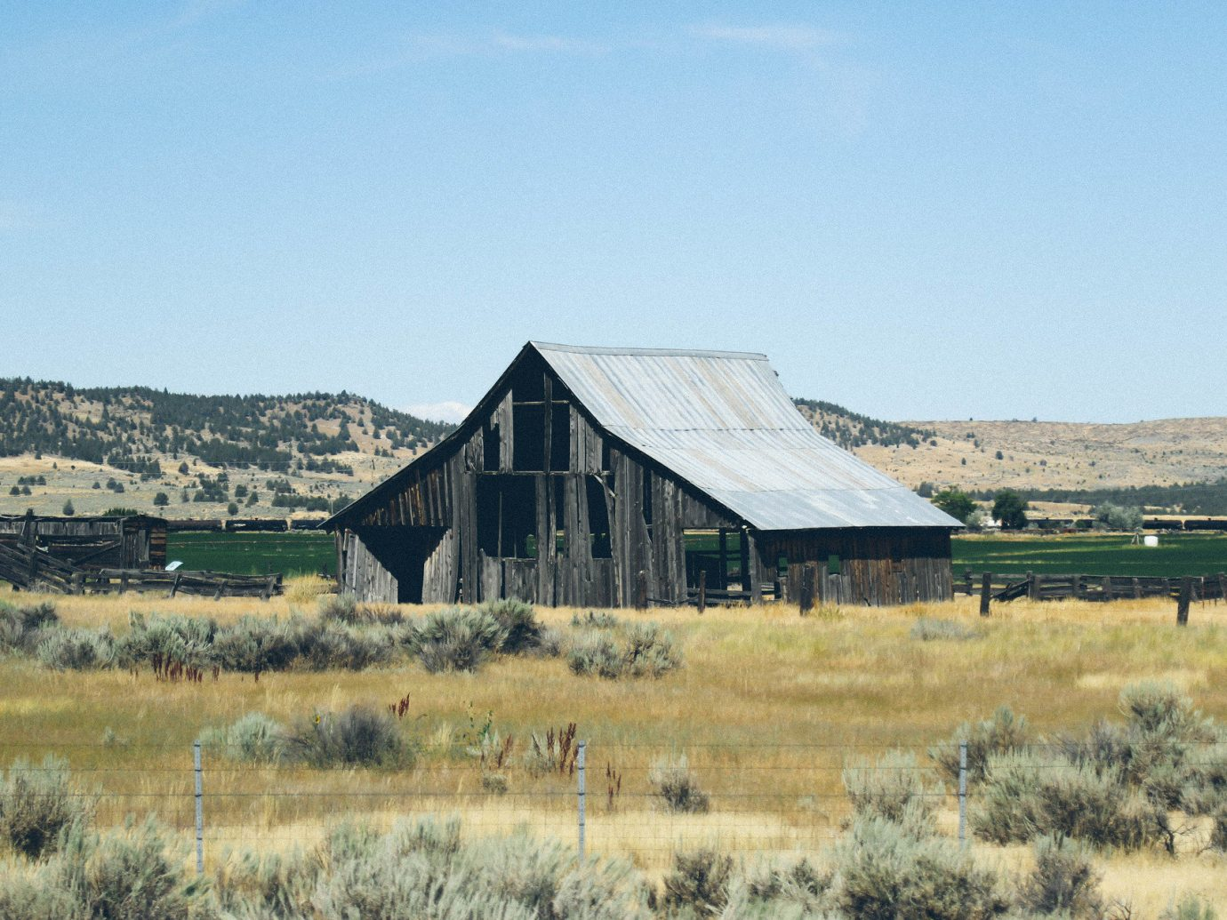 Jetsetter Guides Road Trips grass outdoor sky field building barn farm building pasture natural environment plain prairie grassland Farm rural area steppe landscape grassy Ranch house dry stable lush