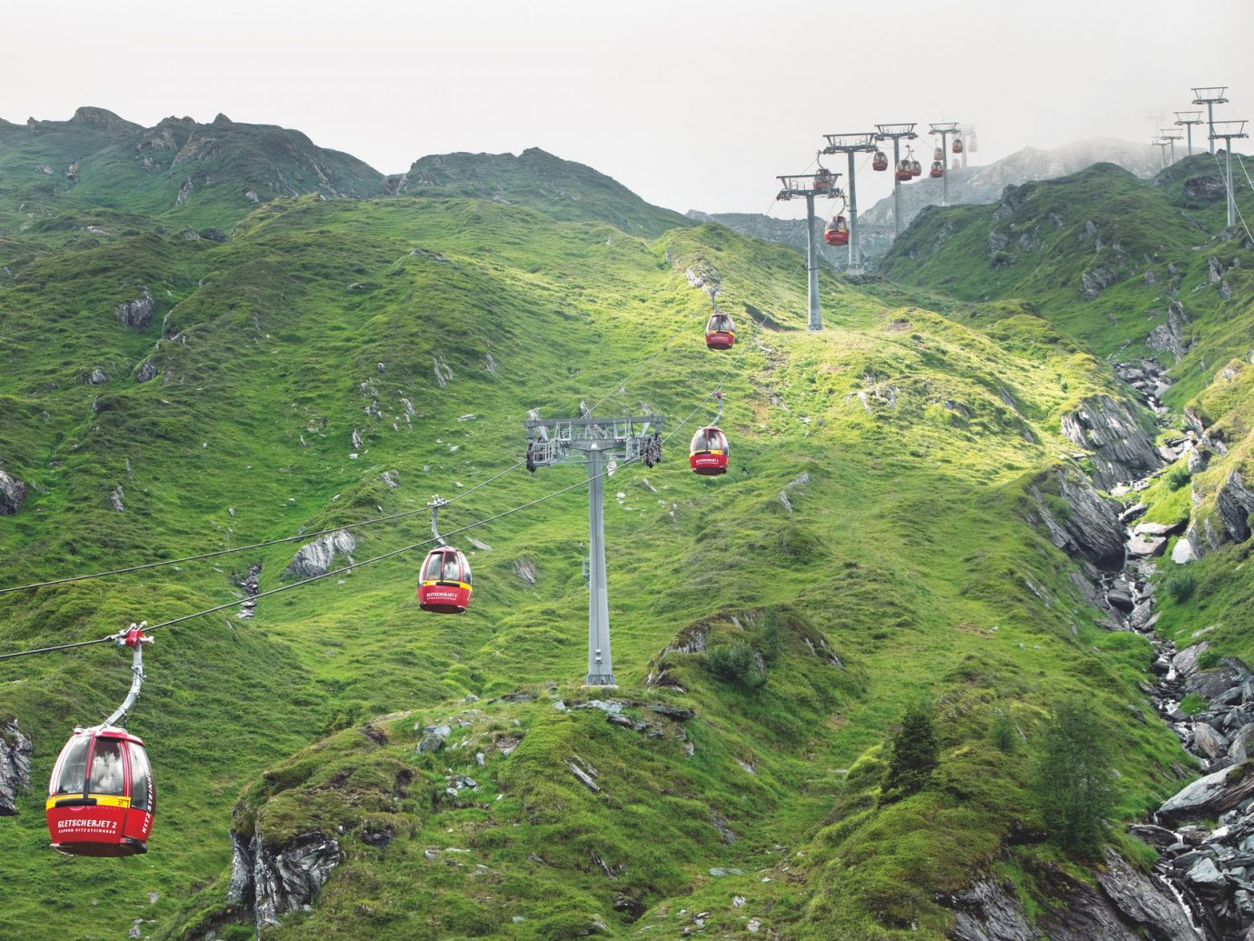 cable car europe gondola Greenery Lakes + Rivers Mountains Outdoor Activities Outdoors Outdoors + Adventure remote summer trolley mountain sky outdoor grass hill mountainous landforms Nature mountain range geological phenomenon hillside ridge mountain pass trail terrain extreme sport Adventure alps screenshot plateau Jungle aerial photography slope lush highway highland