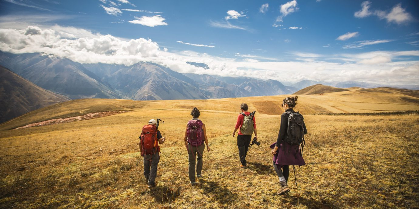 Adventure backpackers hike hikers hiking Mountains Nature Outdoor Activities Outdoors people remote serene Travel Tips sky outdoor grass mountain mountainous landforms wilderness field grassland horizon hill morning walking landscape mountain range plateau sunlight highland megalith