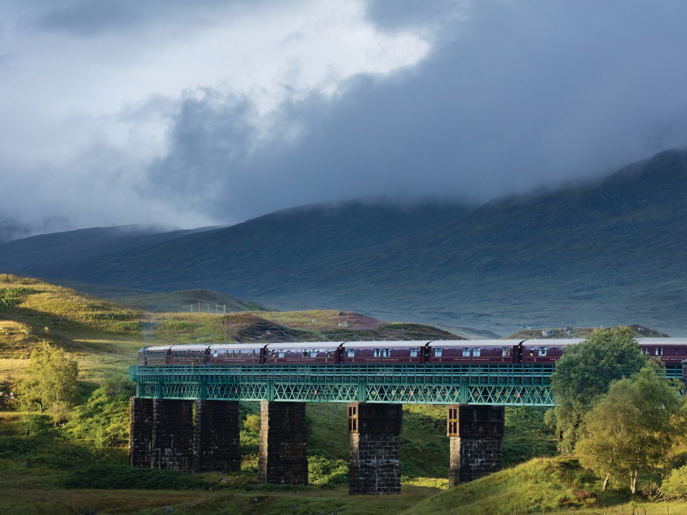 Romance Trip Ideas grass outdoor train sky highland track mountainous landforms mountain transport atmospheric phenomenon cloud hill mountain range green morning rural area landscape infrastructure traveling reservoir bridge valley highway engine lush