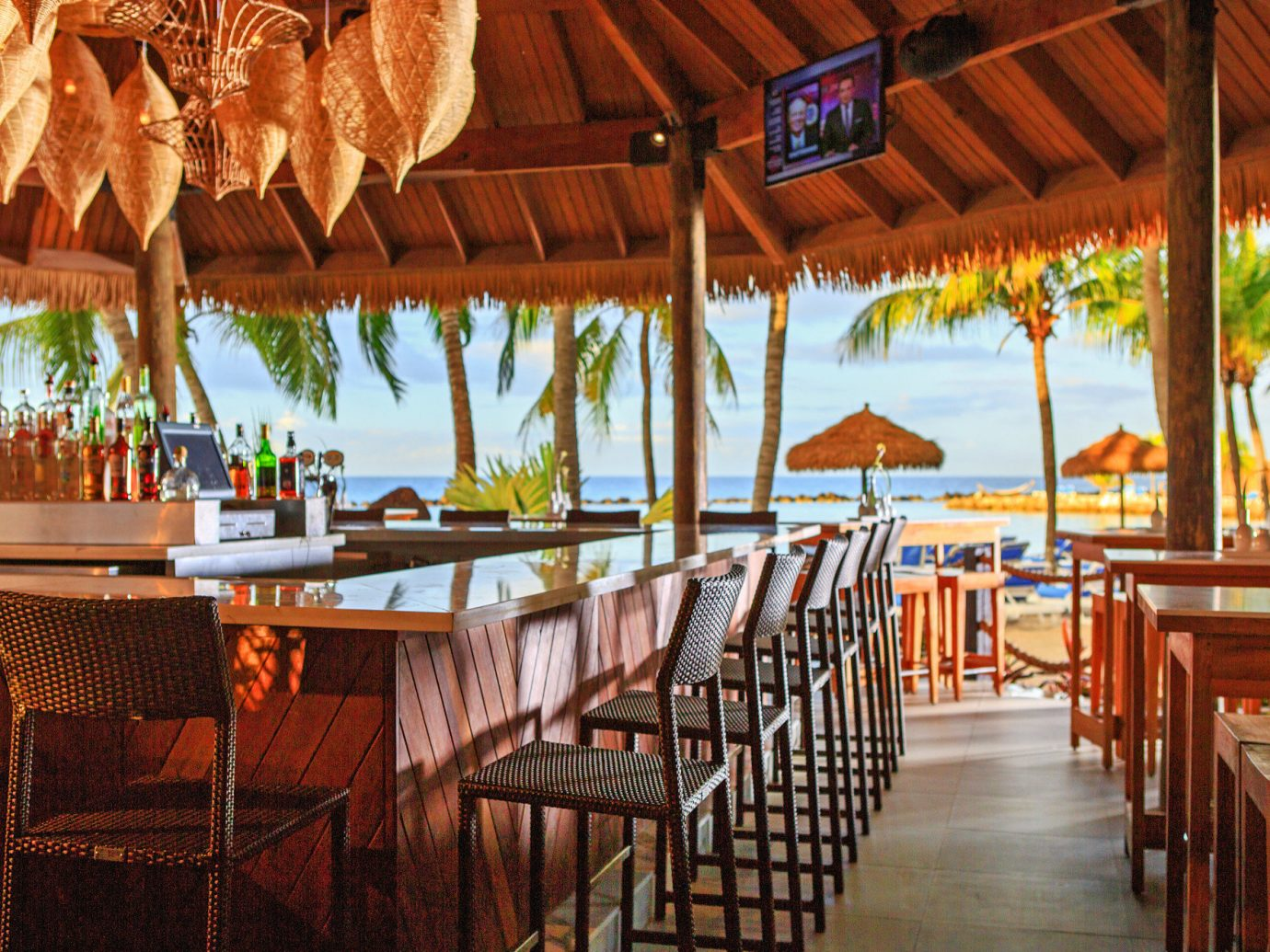 Aruba Bar Beachfront Budget caribbean Dining Drink Eat Hotels Party table chair floor Resort restaurant wooden vacation meal estate hacienda eco hotel area set furniture several dining room dining table