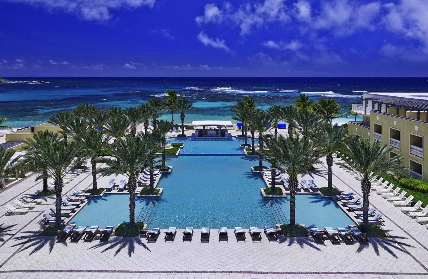 Hotels water outdoor sky Resort Beach swimming pool resort town palm tree caribbean Ocean arecales tropics vacation leisure shore tourism real estate condominium hotel estate Deck Sea tree palm lined overlooking sandy