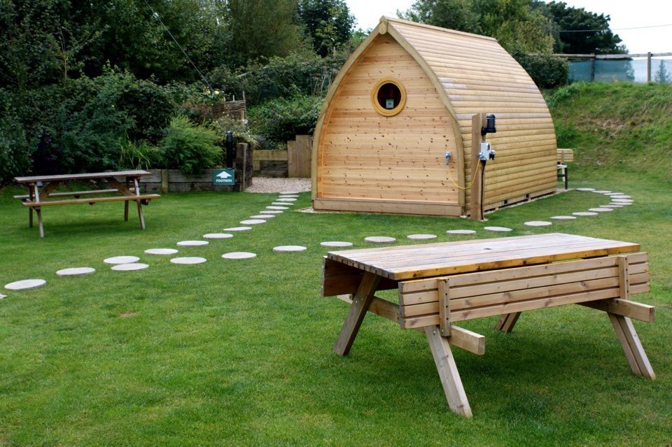 Festivals + Events Glamping Offbeat Outdoors + Adventure Trip Ideas Yoga Retreats grass bench outdoor tree wooden park Picnic backyard lawn cottage furniture outdoor structure grassy wood seat lush