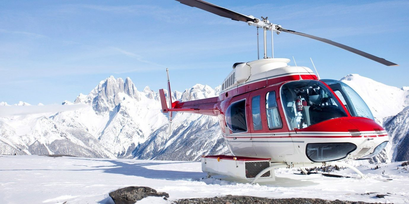 Mountains + Skiing Outdoors + Adventure sky snow outdoor vehicle snowmobile transport geological phenomenon Ski piste winter sport ski equipment alpine skiing skiing mountain range downhill slope helicopter