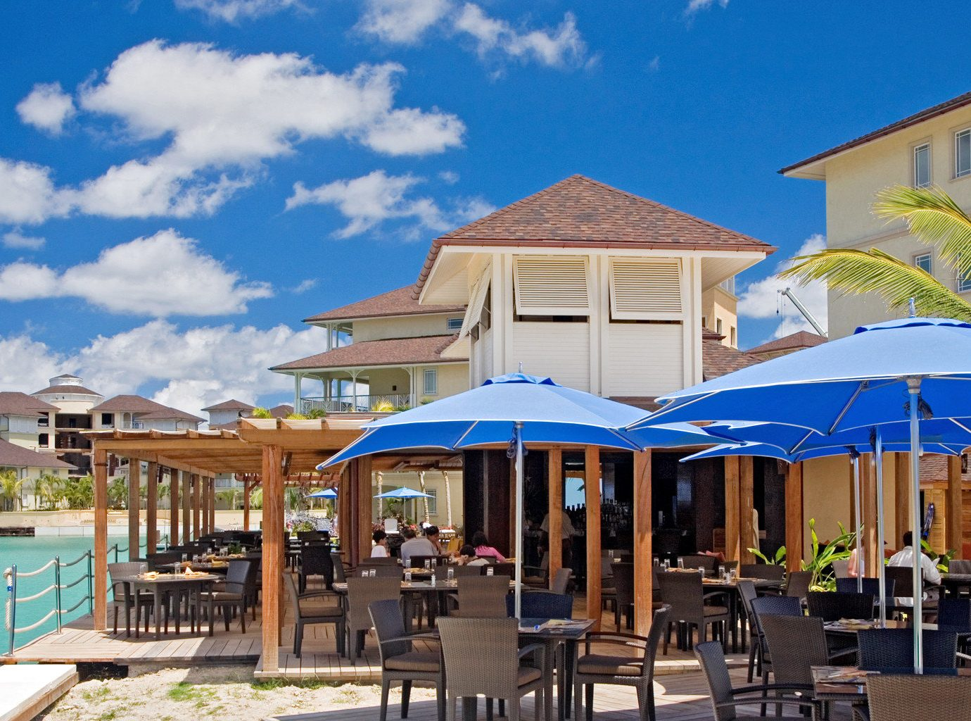Beach Beachfront Dining Drink Eat Grounds Hotels Island Romance outdoor chair sky table umbrella leisure property Resort Deck lawn vacation estate wooden real estate restaurant Villa set furniture several shore
