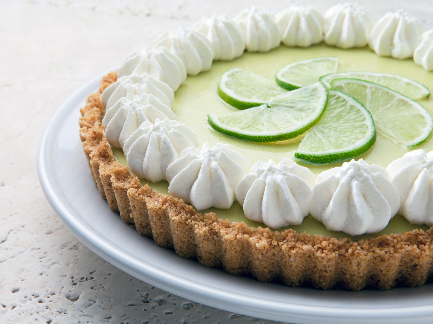Food + Drink plate food dish dessert slice key lime plant produce sour cream citrus lime land plant baked goods fruit torte cream pie coconut icing key lime pie pie flowering plant cheesecake flavor whipped cream sliced cream