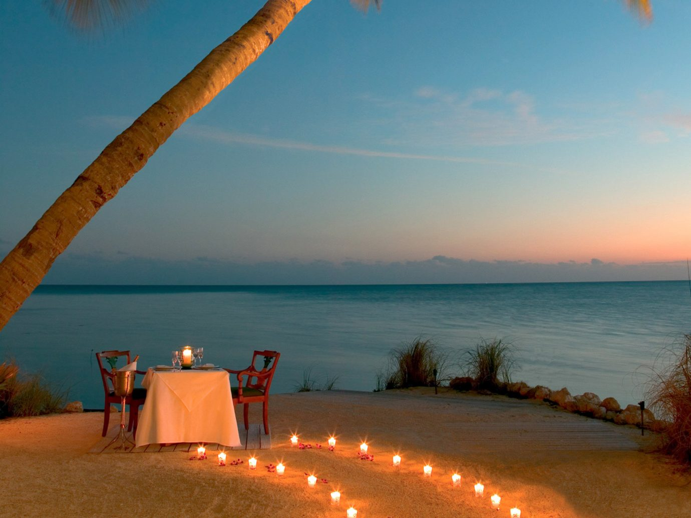 Beach Beachfront Dining Drink Eat Hotels Island Outdoors Resort Romance Romantic Scenic views Sunset Trip Ideas Waterfront sky water outdoor Sea Ocean horizon Coast vacation morning evening sand dusk sunrise Nature sunlight arecales cape orange tree plant shore