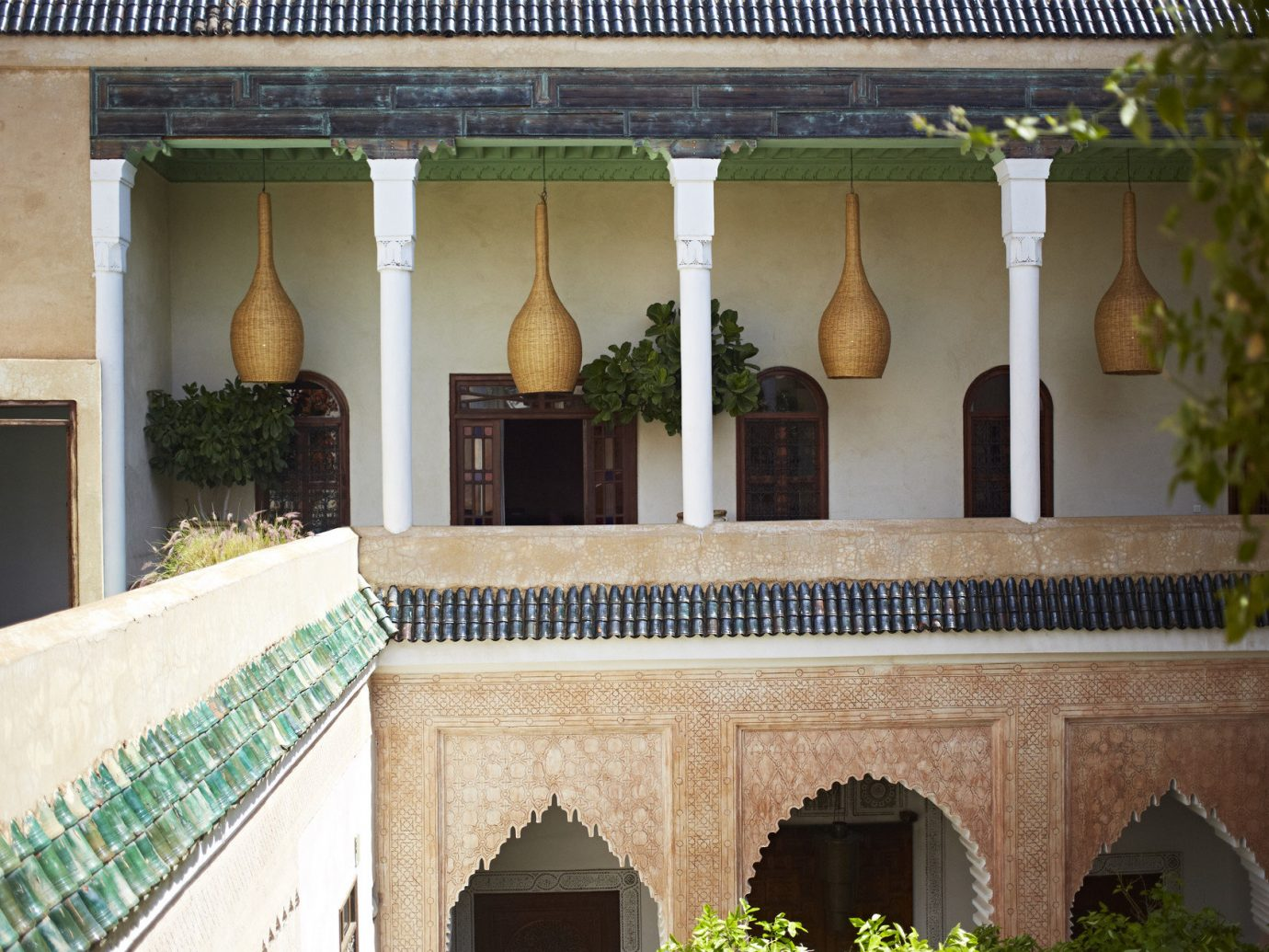 Arts + Culture Marrakech Morocco Style + Design outdoor property building house Architecture Courtyard hacienda Villa baluster estate palace facade home mansion interior design window arch stone
